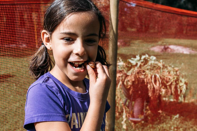 Girl eating a carrot full of dirt