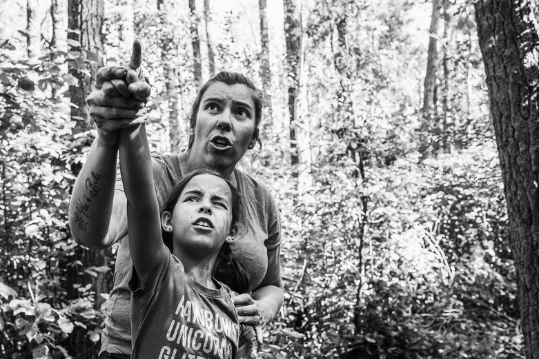 Mother and daughter pointing at something in the forest