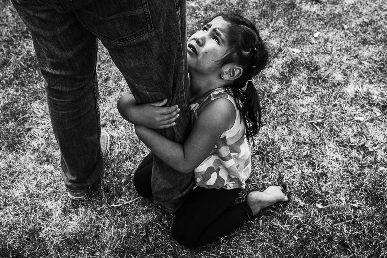 Girl with teary eyes holding on to her father's leg